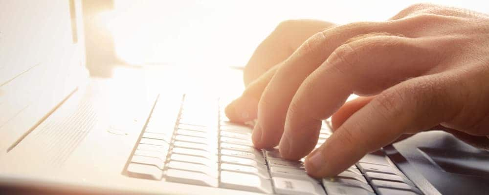 Man's hands typing on laptop keyboard