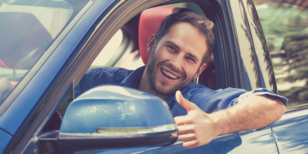 Man Giving Thumbs Up After Buying a Used Car
