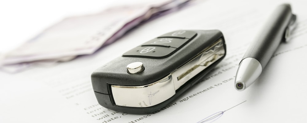 Car key and pen on financing documents