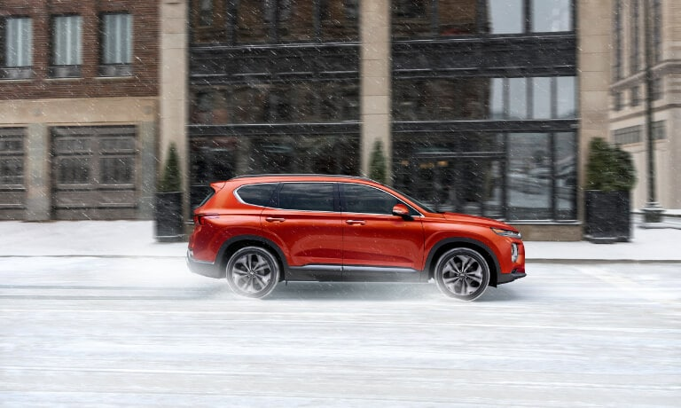 2020 Hyundai SantaFe in orande side view from the passanger side driving in the snow throughout a town