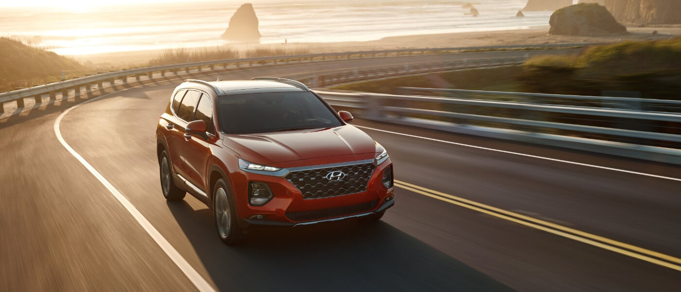2020 Hyundai Santa Fe in red driving on a highway in the mountians