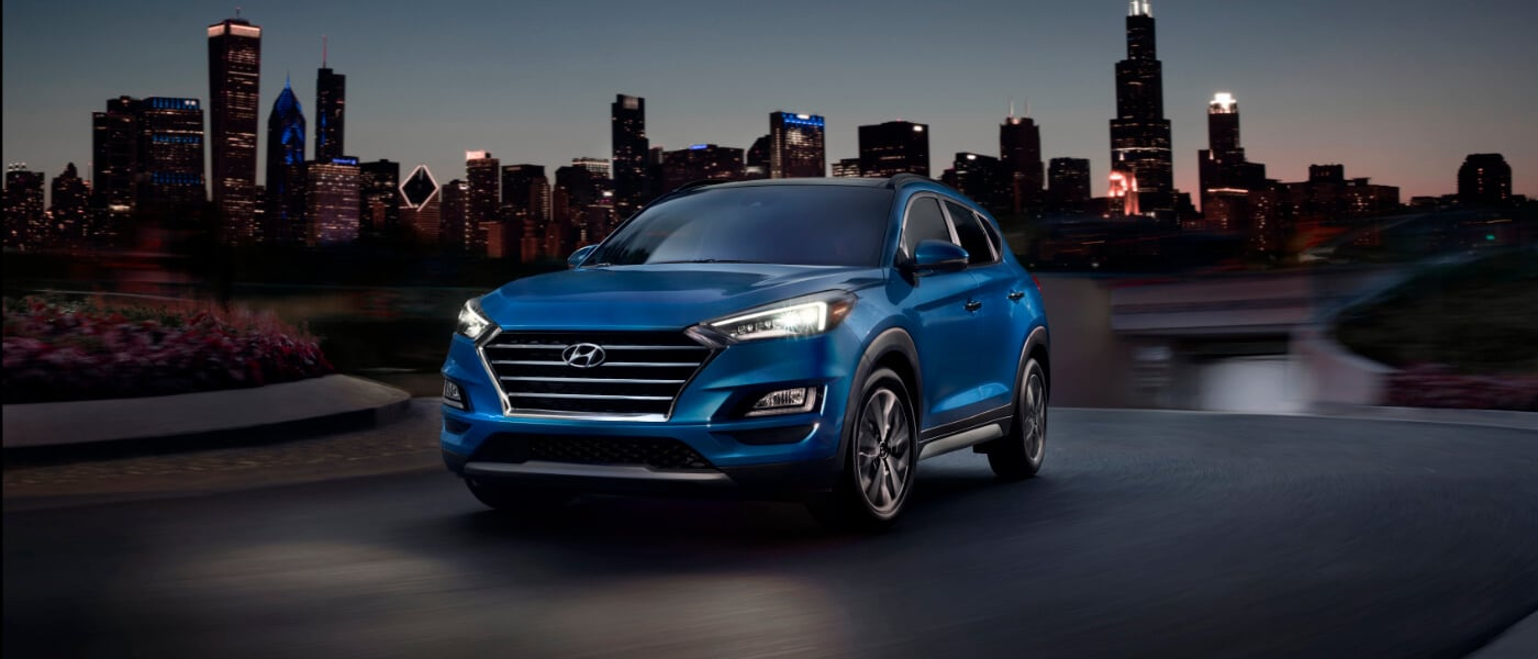 2020 Hyundai Tucson in blue driving on curve at night with the chicago skyline behind it