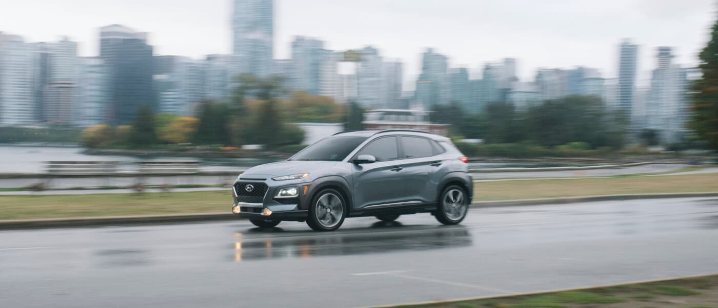 Silver 2020 Hyundai Kona driving on a road in the rain against a city skyline