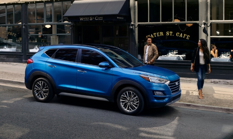Couple walking to Blue 2020 Hyundai Tucson
