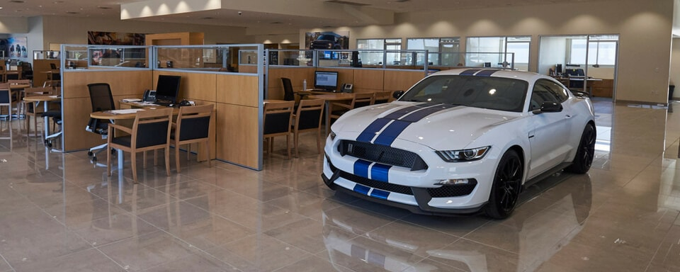 AutoNation Ford Arlington's Finance Center with a new Ford Mustang for sale in the showroom