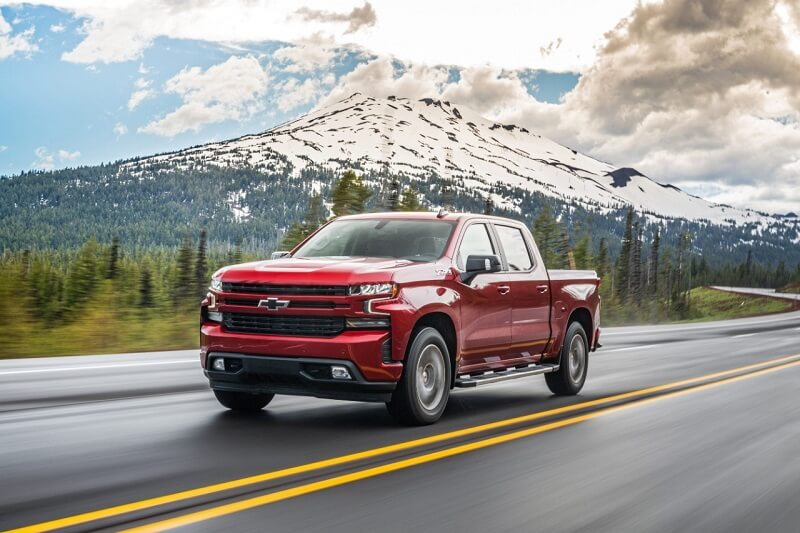 Image of a red GMC pickup driving down the highway