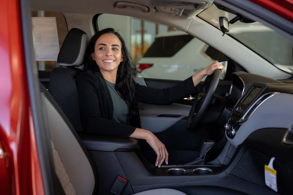 Image of a woman smiling in the driver's seat of a red car