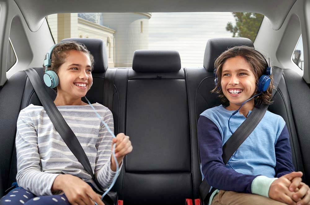 Image of a two kids in the backseat wearing seatbelts