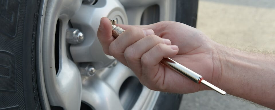 Checking tire pressure with a gauge