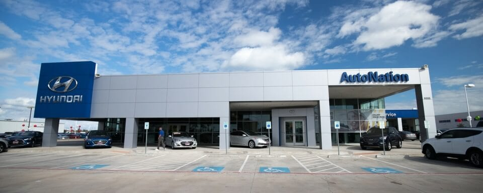 Exterior shot during the day of AutoNation Hyundai Corpus Christi, an auto dealership where cars and SUVs are sold.