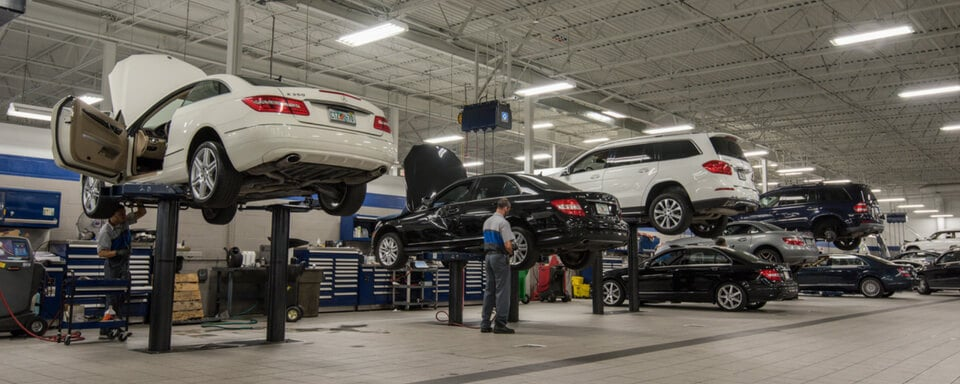 Inside a Florida Mercedes-Benz service center with a technician performing repairs