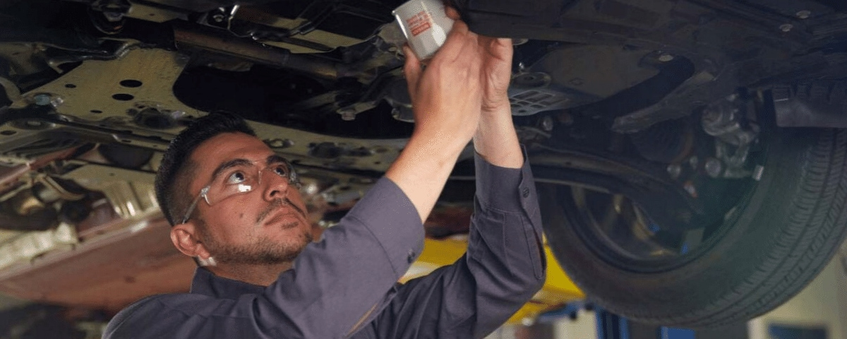 Nissan technician performing an oil change