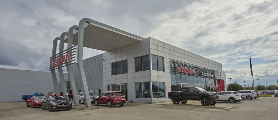Exterior entrance to AutoNation Nissan Katy dealer during the day