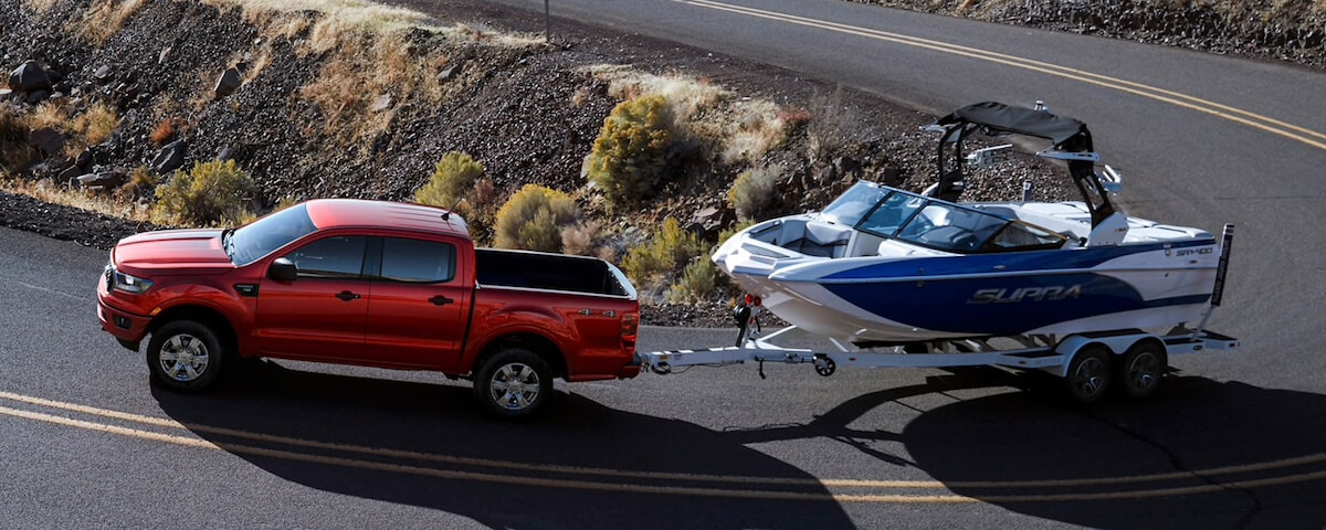 2019 Ford Ranger towing a boat on a winding road