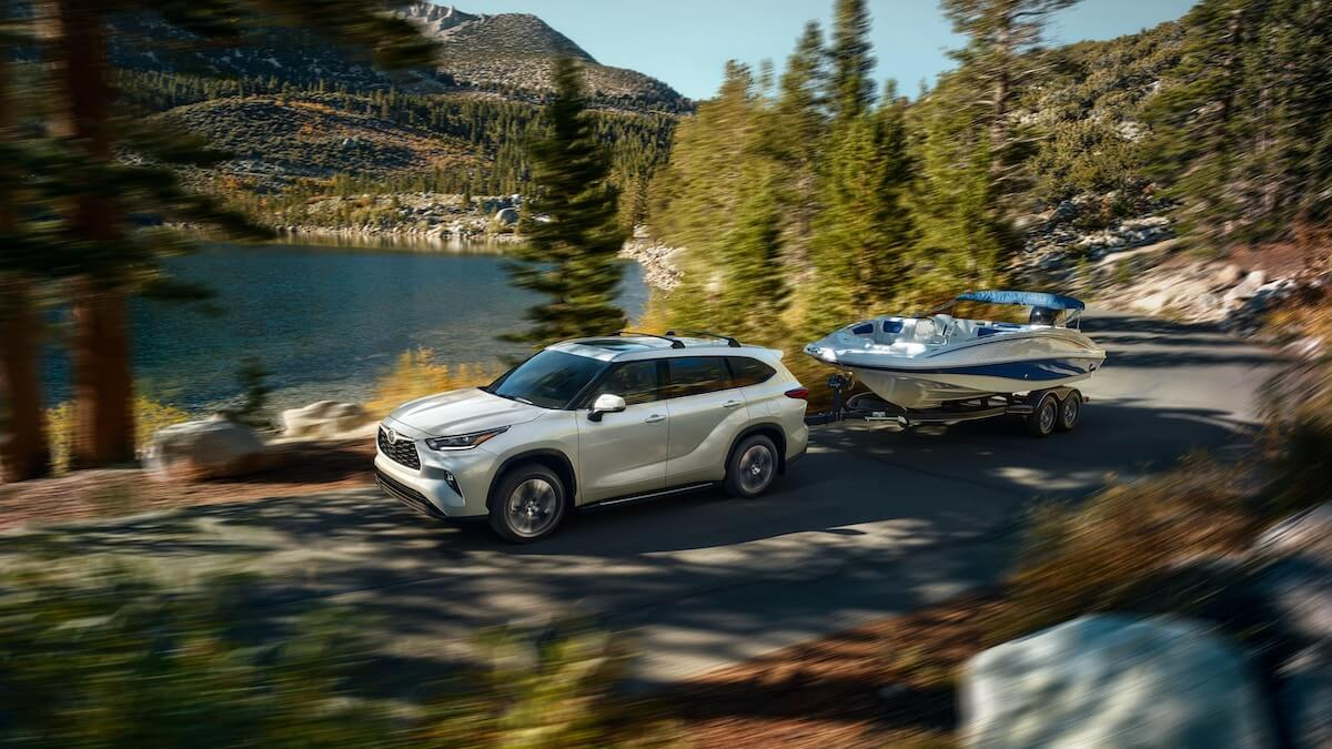 2021 Toyota Highlander XLE AWD in Blizzard Pearl towing a boat