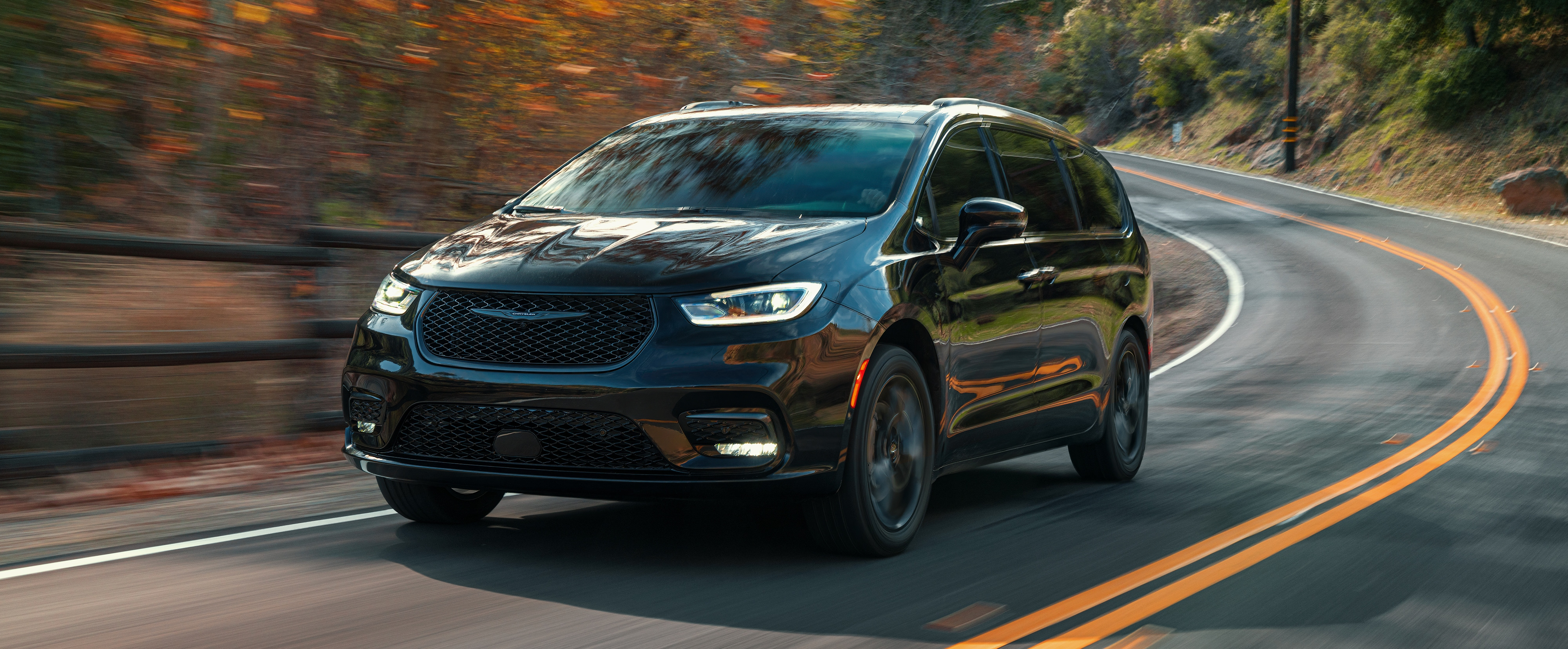 2021 Chrysler Pacifica driving on a road in front of red and gold fall trees; Chrysler Pacifica is available at our RI Dealership