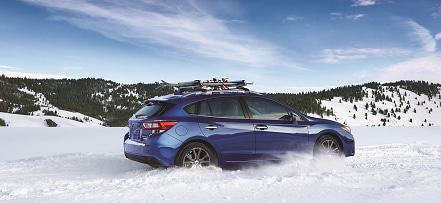 Subaru SUV driving in snow
