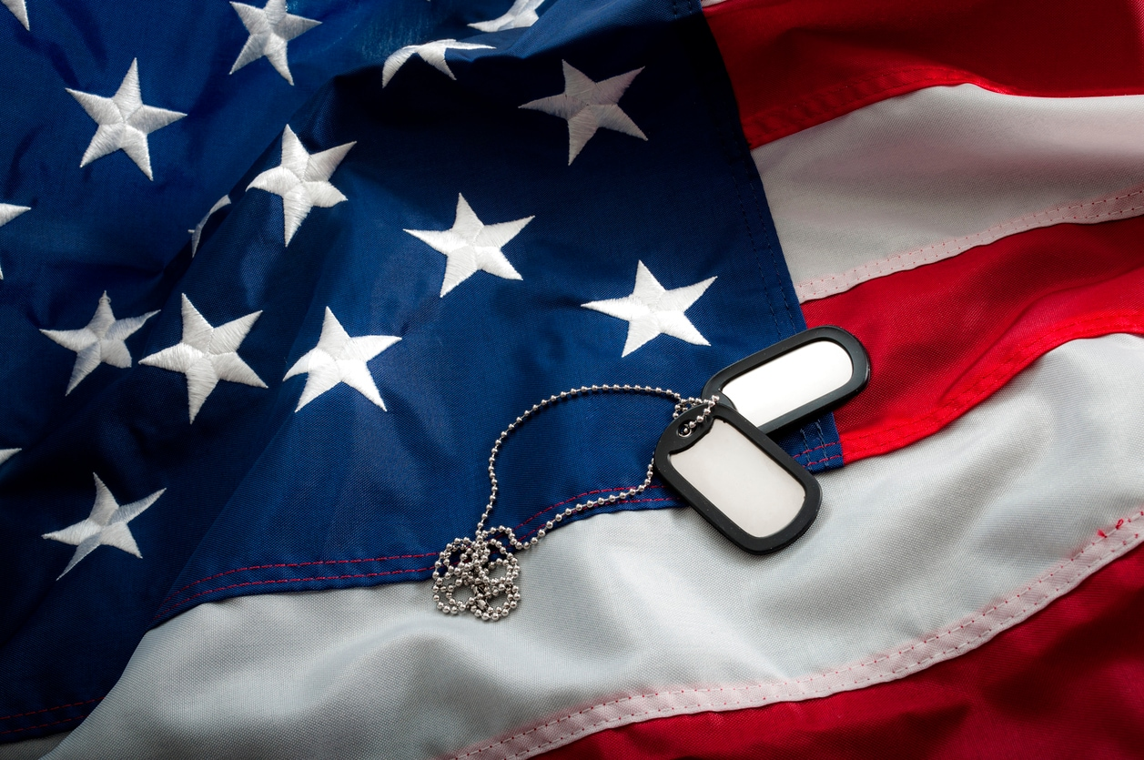 Military dog tags laying across American Flag