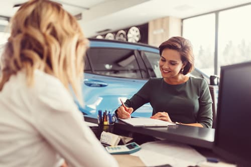 Woman signing lease papers at dealership
