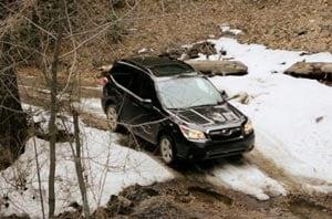 Subaru Vehicle Driving Through Snow