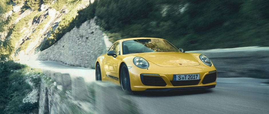 A yellow Porsche 911 Carrera driving down the open road