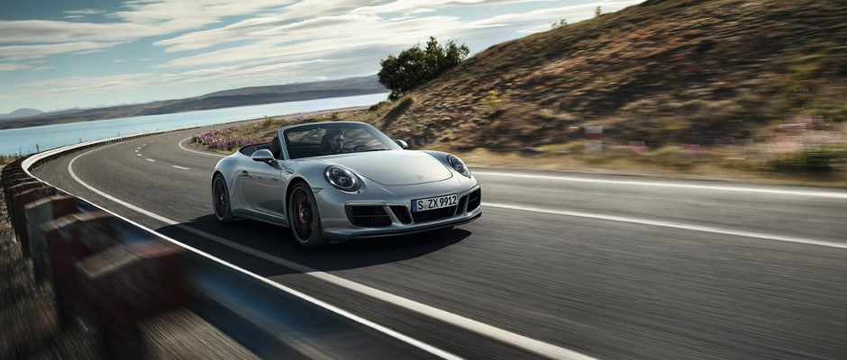 A Porsche 911 Targa 4 driving around a curved open highway