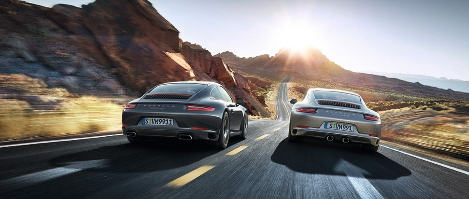 Two Porsche cars driving down an open road