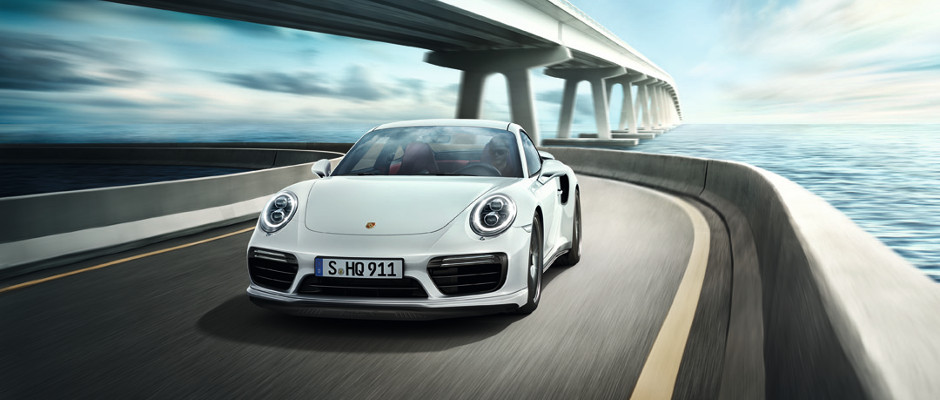 A white Porsche Turbo driving over a bridge