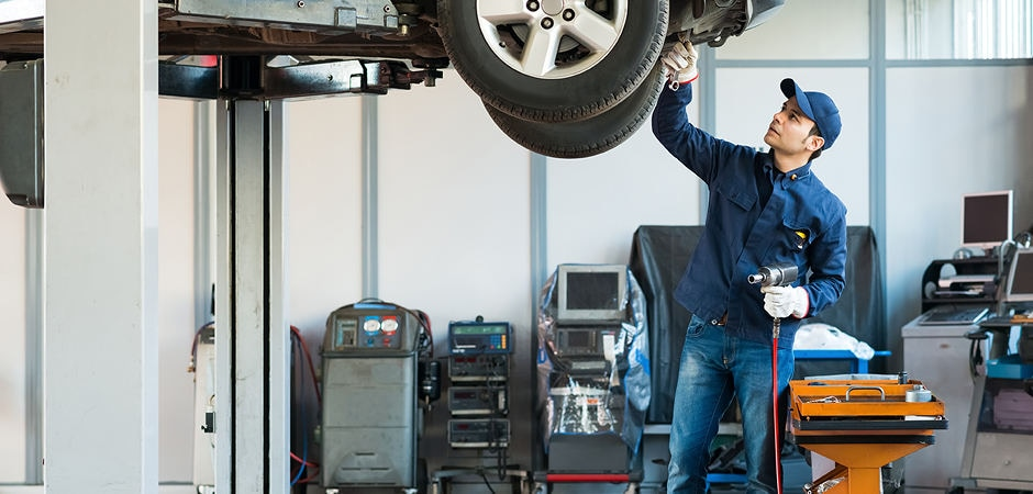 A mechanic adjusting the tire alignment on a vehicle