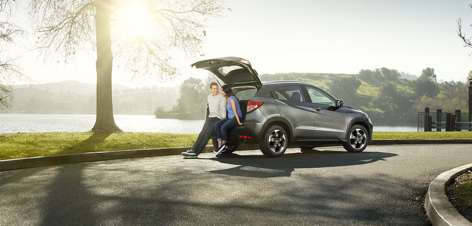 Two people sitting on the back of an HR-V at a park