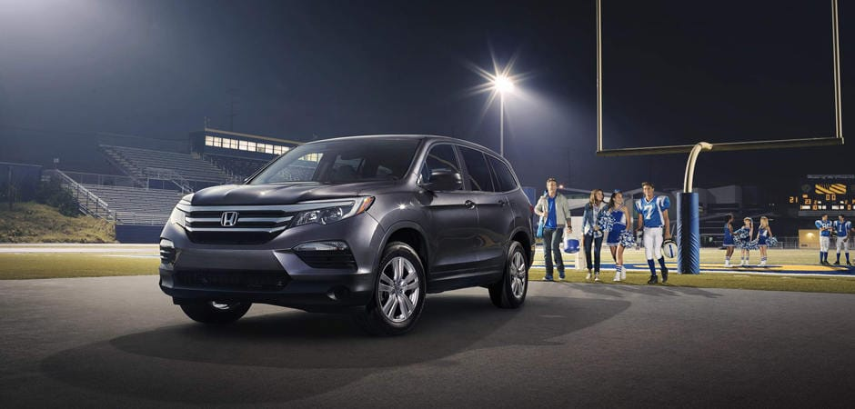 A dark grey Honda Pilot parked near a football field