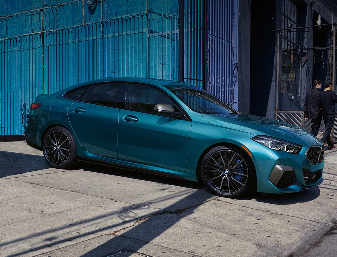 A blue metallic BMW 2 Series Gran Coupe pulling out of alley