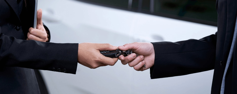 Person trading in keys to car dealership salesman