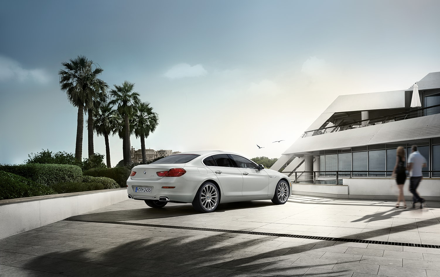 BMW of Rockville is a car dealership near Glen Echo MD | White 2018 BMW 6-Series parked by modern architecture and palm trees