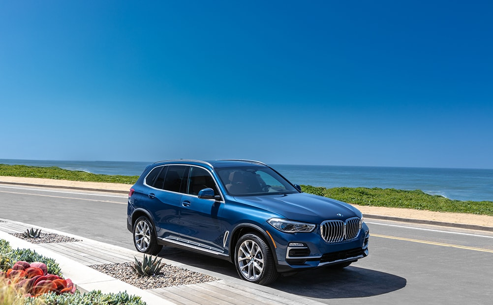 BMW of Rockville is a car dealership near Glen Echo MD | Blue 2020 BMW X5 driving near water