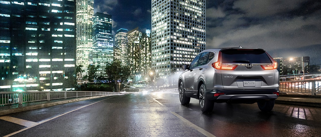 Rearview of a silver CR-V driving into the city at night