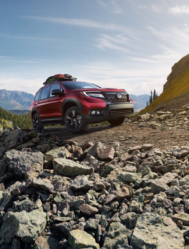 What you can get to personalize your vehicle at Bobby Rahal Honda in State College | Red Honda Passport driving up a cliff