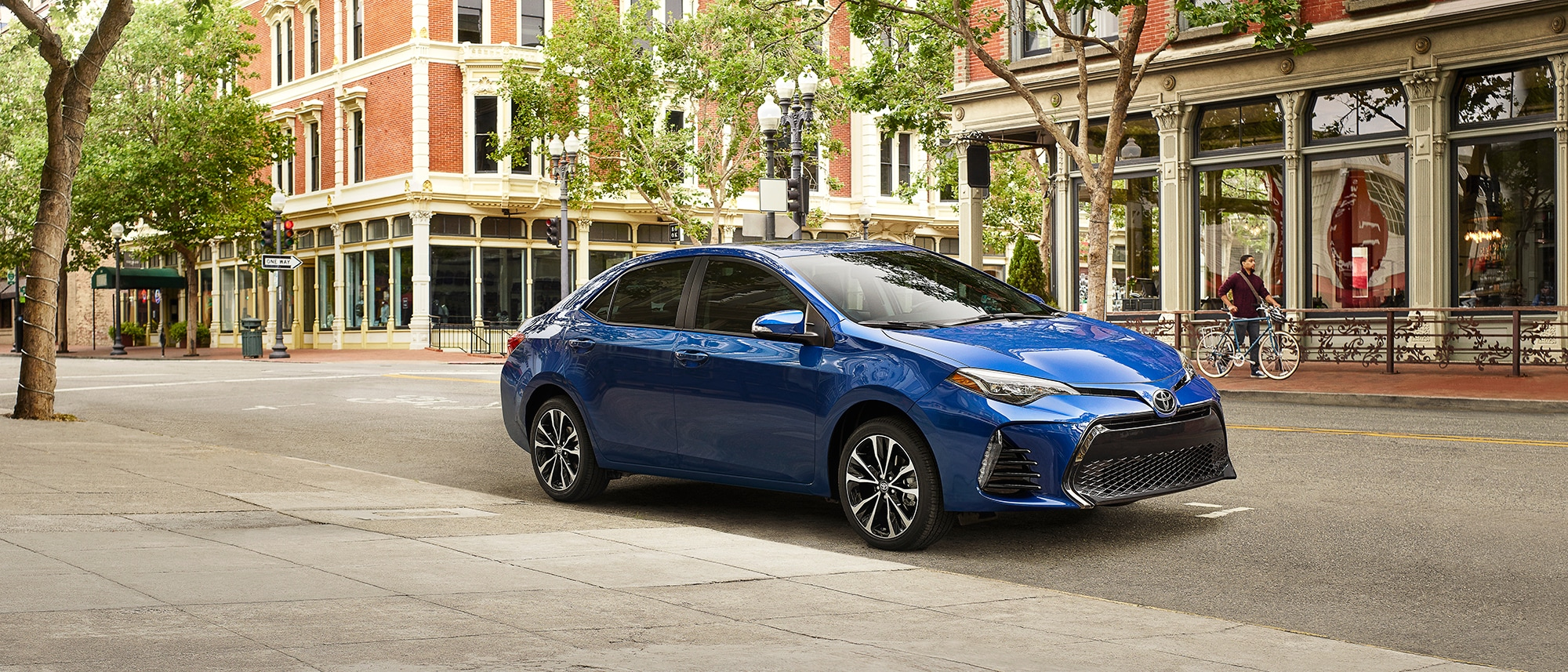 blue 2019 corolla driving down a street