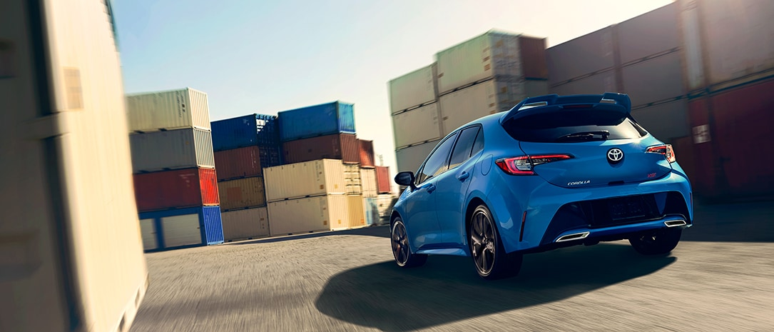 rearview of a 2019 corolla hb driving fast through a shipping container track