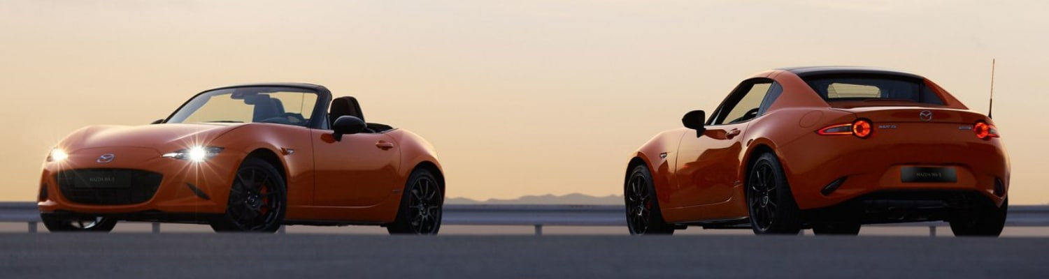 An orange 2019 Mazda Miata MX-5 and 2019 Mazda MX-5 RF parked in an open lot in front of a vibrant orange sunset