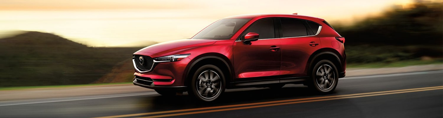 Driver side view of a used 2018 Mazda CX-5 SUV driving down an open road with blurred street lines