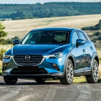 Front driver side view of a blue 2019 Mazda CX-3 parked on an open country road as the sun reflects of the driver's door