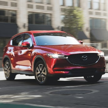 Front passenger side of a red 2019 Mazda CX-5 driving around a street corner as the sun glares off the headlight