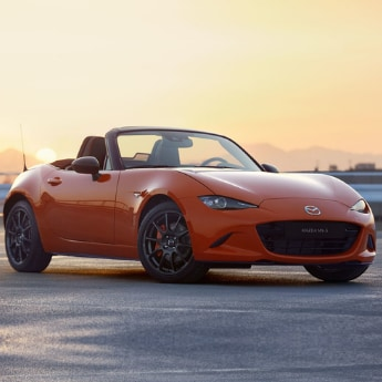 Front passenger angle of an orange 2019 Mazda Miata MX-5 parked in an open concrete parking lot with a beautiful orange sunset in the background