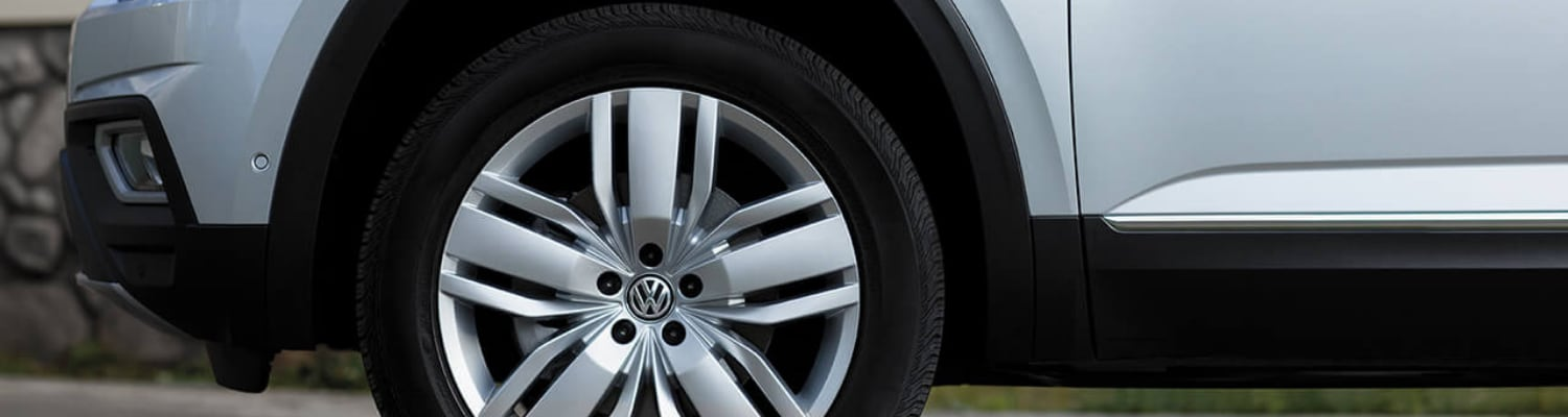 Zoomed view of the front driver side tire on a 2019 VW Atlas focused on the VW logo in the tire rim