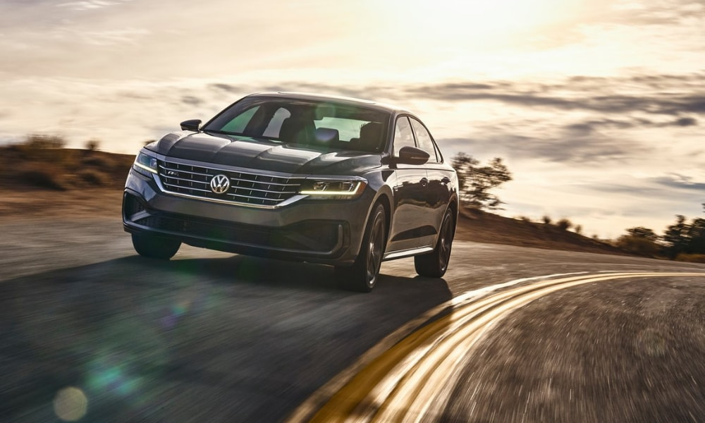 2020 VW Passat at high speeds around a curved road at sunset camera glares