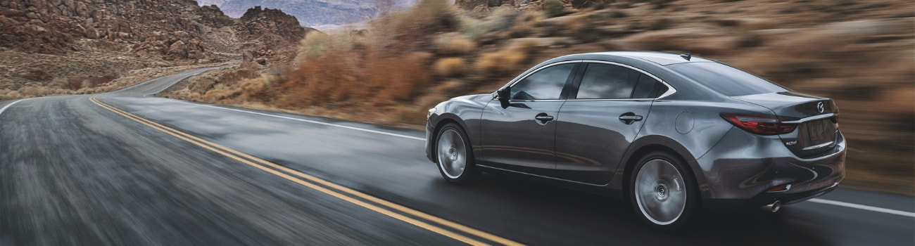 Driver side of a gray 2019 Mazda6 driving down a curvy road by a mountain range