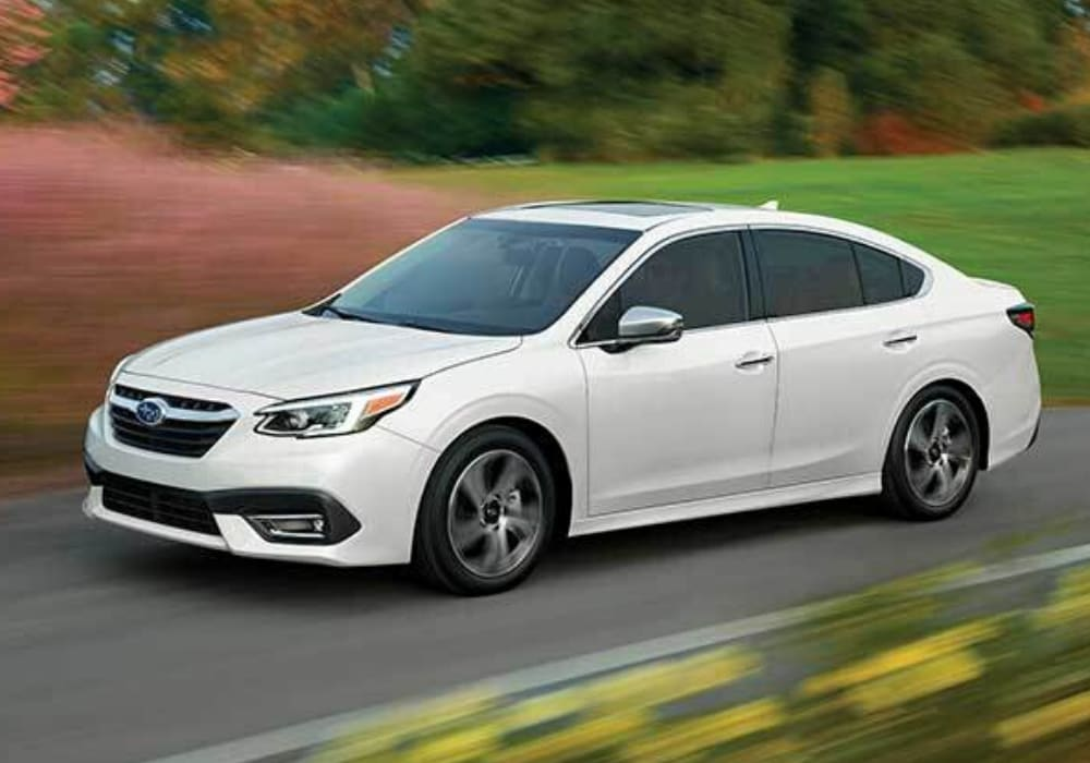 White 2020 Subaru Legacy driving down an open road on a cloudy overcast day