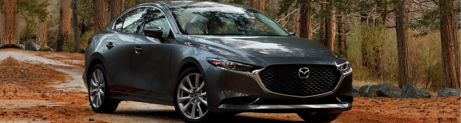 2019 Mazda3 sedan parked on a road covered in pine straw in a forest