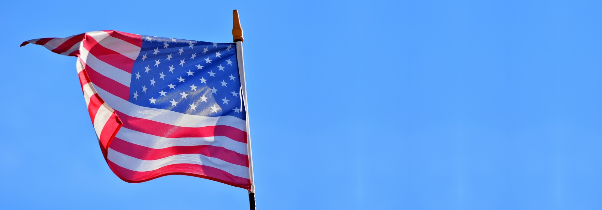 American Flag blowing in the wind blue sky behind
